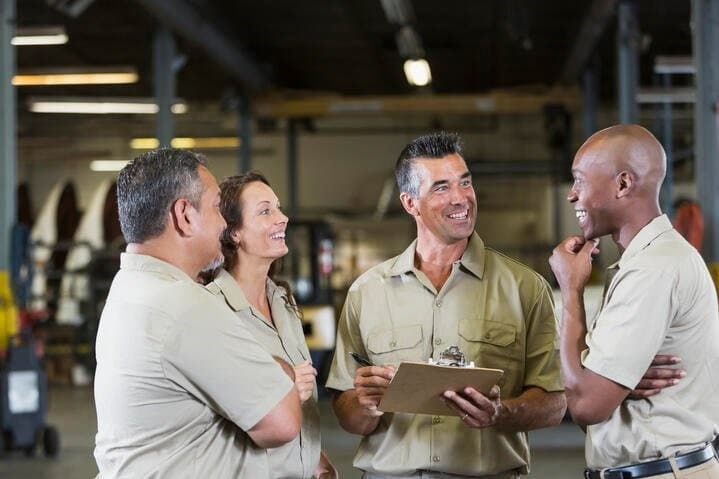 4 motor carrier professionals standing in a group talking