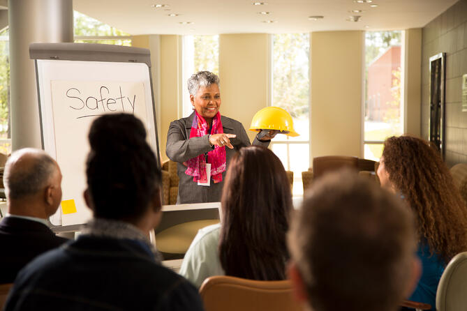 woman holding a construction hat standing in front of an audience of employees during a safety meeting