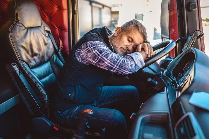 truck driver sleeping on semi steering wheel